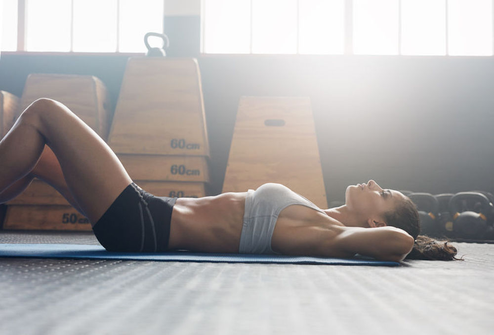Image depicts a woman bracing her core during core exercises