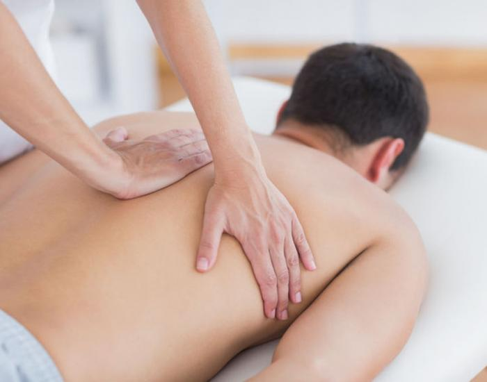 Therapist doing back massage showing what is remedial massage