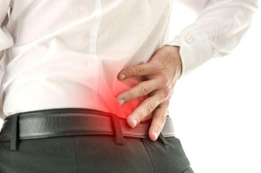 Image of a man holding his back due to low back pain