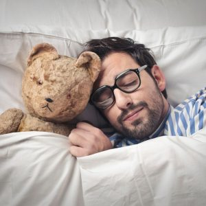 Image of a man getting to sleep with his bear